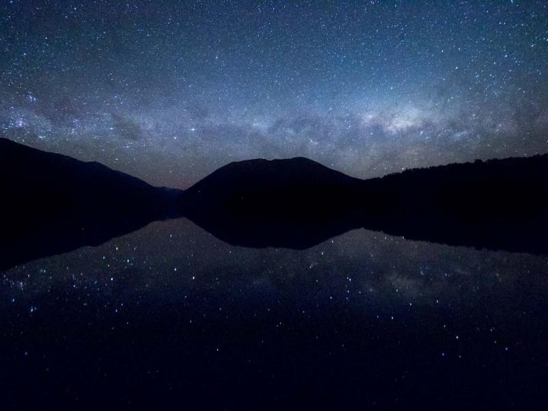 """(Aparté, c'est un de mes clichés dont je suis le plus fier en Voie lactée. Je l'ai vendu en tableau sur commande suite à mon vernissage de l'expo. C'est aussi une chose que j'aimerai parlé sur mon fb.) Photo prise lors de mon dernier mois en NZ, au lac Nelson Lake, south Island. C'est la fin de la saison de la Voie Lactée, elle se couche à l'horizon. J'ai profité de cette nuit calme pour aller voir ce ciel """"martelé"""" (*mot à changer) d'étoiles. Par chance le lac était d'un calme. J'ai donc pu obtenir un bel effet miroir avec les ombres chinoises du terrain environnant. Un moment magique que je n'oublierai jamais surtout gràce à ce cliché"""